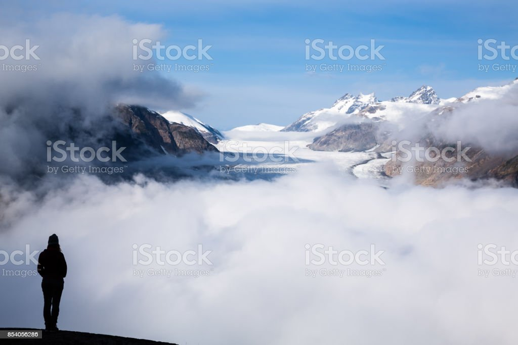 Silhouette of young woman standing above the Salmon Glacier stock photo