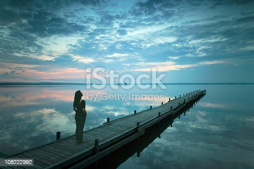 Rear view on Young woman standing lakeside on jetty watching magical clouds at dusk. Exposure with extreme wide-angle lens at Lake Steinhuder Meer in Lower Saxony, Germany.