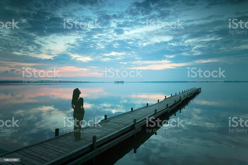 Silhouette of Young Woman Standing On Lakeside Jetty at Dusk stock photo