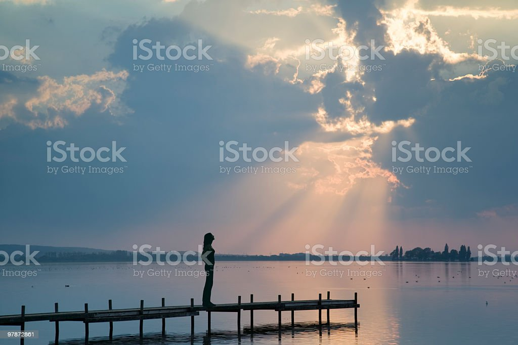 Silhouette of young woman standing on lakeside jetty in sunbeam royalty-free stock photo