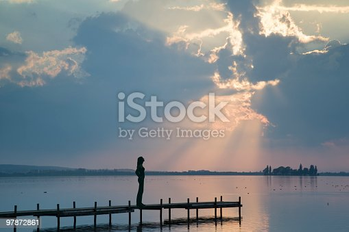 Side view of Young woman standing lakeside on jetty watching magical sunbeam effect at dusk. Location: Lake Steinhuder Meer in Lower Saxony, Germany.