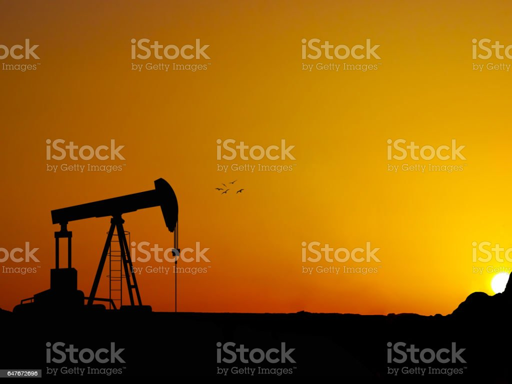 Silhouette oil well beam pump with nice sunset stock photo