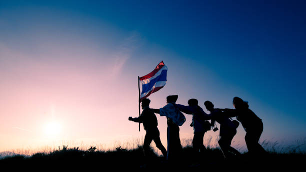 Silhouette on Group of people holding Thailand flag and Move forward over head in sunset sky evening time. Abstract and texture of teamwork and success. stock photo