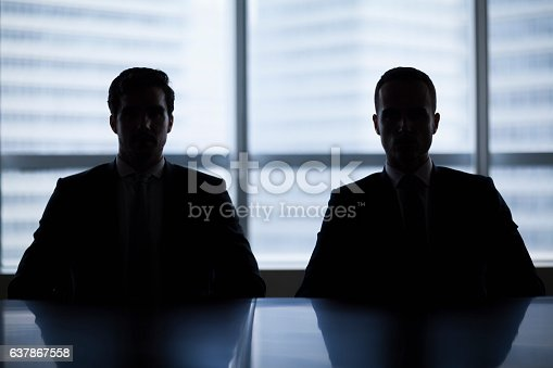 Silhouette pair of businessmen in meeting room