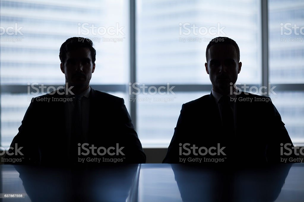 Silhouette pair of businessmen in meeting room stock photo