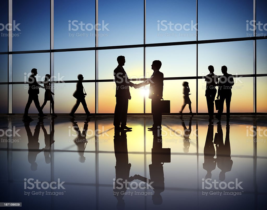 Silhouette people in office building shaking hands stock photo