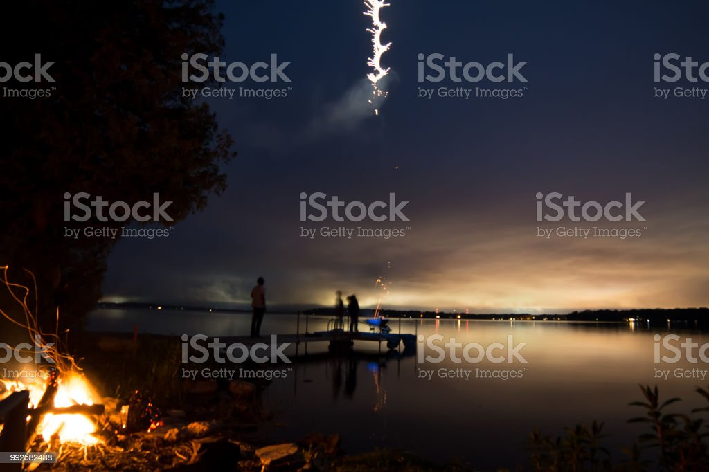Silhouette people with fireworks in sky over beautiful dock at twilight stock photo