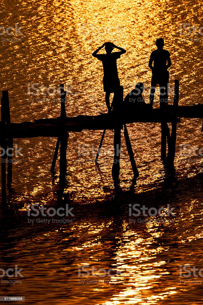 Silhouette photo of children on the wood bridge before sunset. stock photo