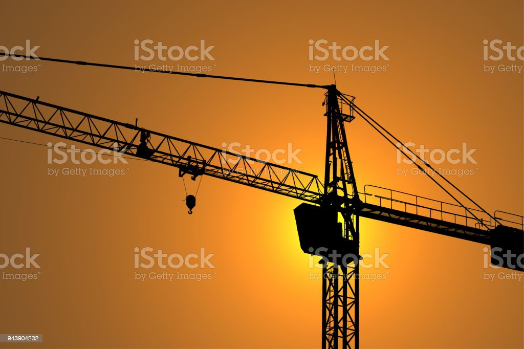 Silhouette photo of crane working on sun flare background in construction concept stock photo