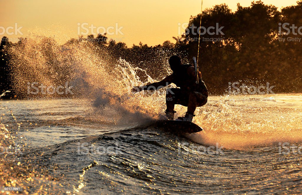 A silhouette photograph of a wakeboarder riding a wave stock photo