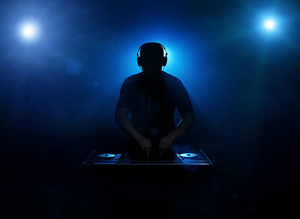 DJ silhouette Silhouette of a disc jockey mixing in the night club with copy space dj stock pictures, royalty-free photos & images