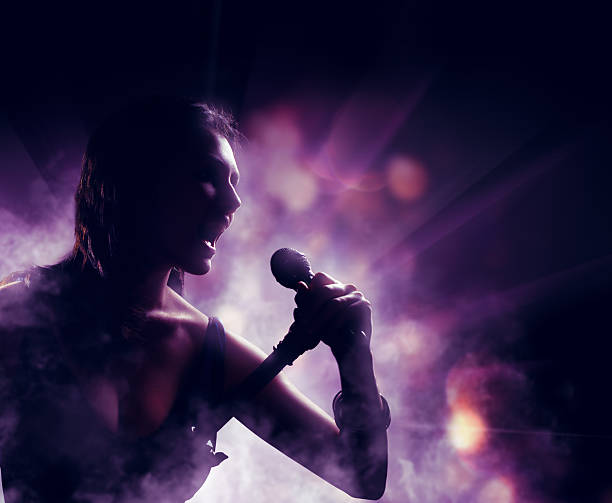 silhouette silhouette of a woman on a background of lights singer stock pictures, royalty-free photos & images