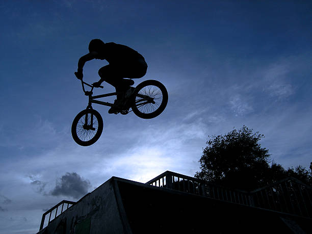 BMX Silhouette BMX rider launching across two ramps at a skatepark. skeable stock pictures, royalty-free photos & images