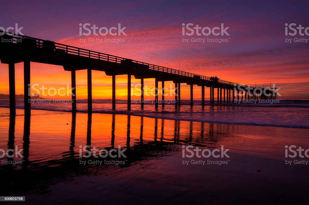 Silhouette pier at beach and brilliant sunset stock photo