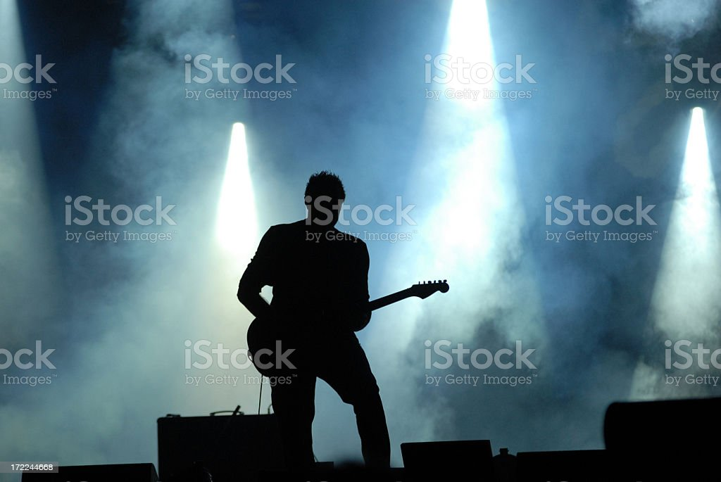 A silhouette playing a guitar at a concert stock photo