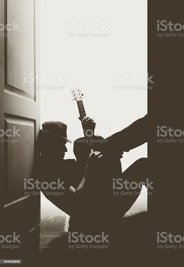 silhouette portrait of male guitarist playing guitar at the door stock photo
