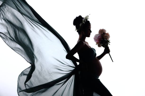 Silhouette Portrait of Pregnant woman hold bouquet flower and fabric fluttering in Air waving fashion style - foto stock