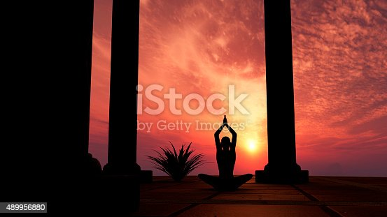 Silhouette practicing yoga at sunset