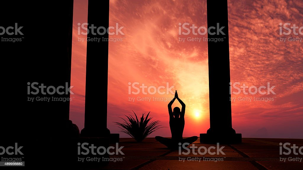 Silhouette practicing yoga stock photo