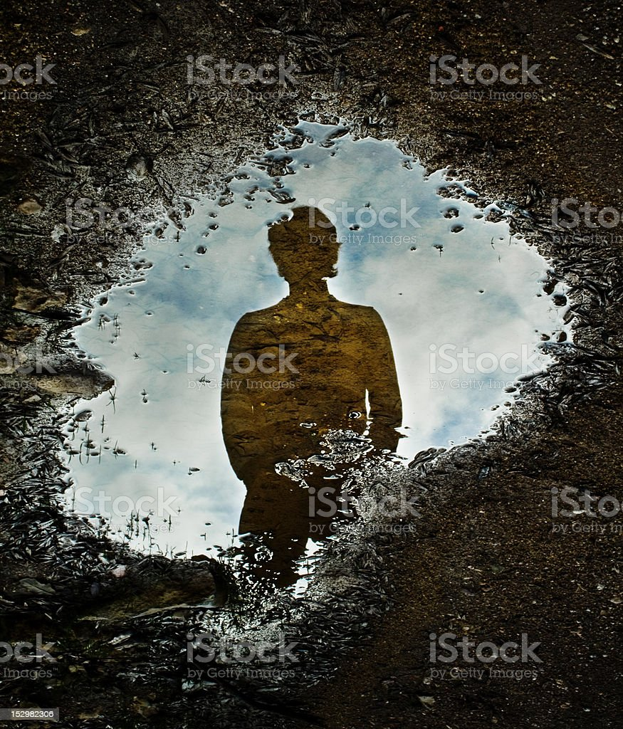 Silhouette reflected on puddle royalty-free stock photo