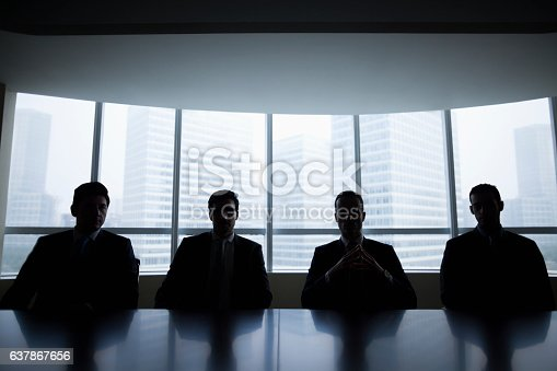 Silhouette row of businessmen sitting in meeting room