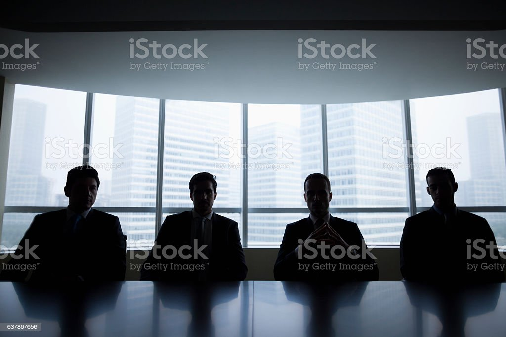 Silhouette row of businessmen sitting in meeting room - foto de acervo