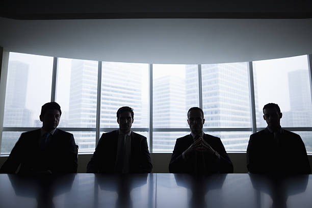 Silhouette row of businessmen sitting in meeting room Silhouette row of businessmen sitting in meeting room negative emotion stock pictures, royalty-free photos & images