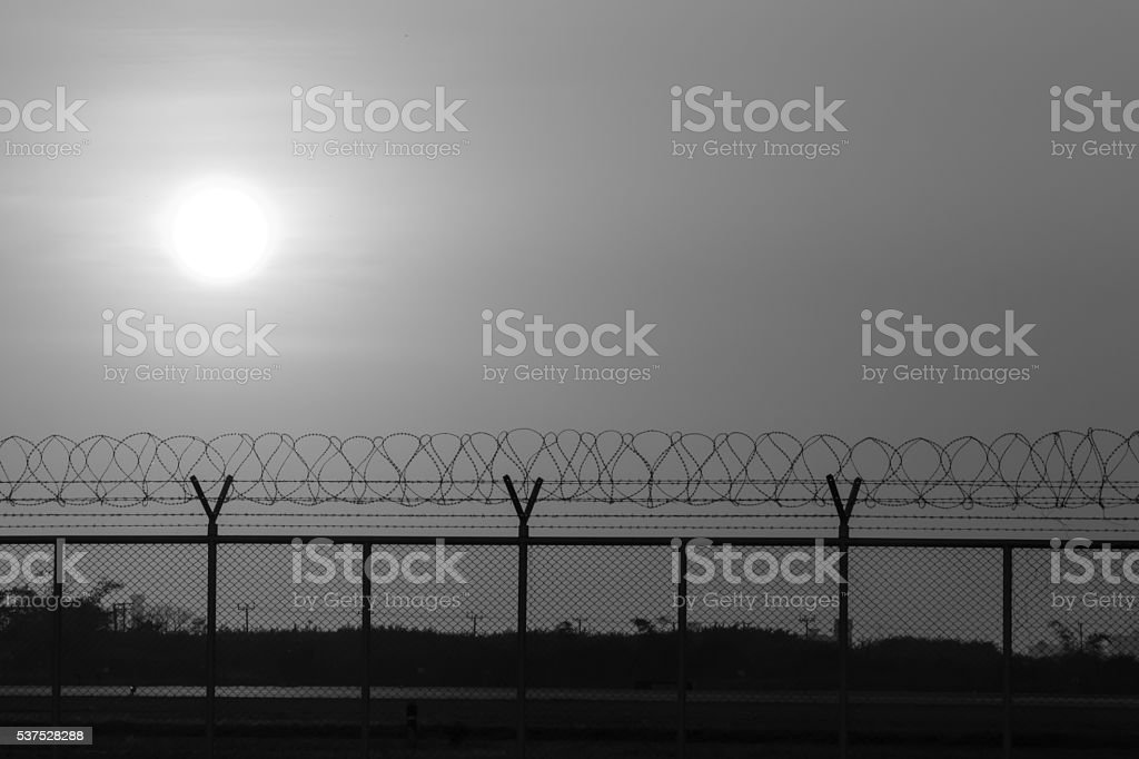 silhouette security with a barbed wire fence at sunset time. stock photo