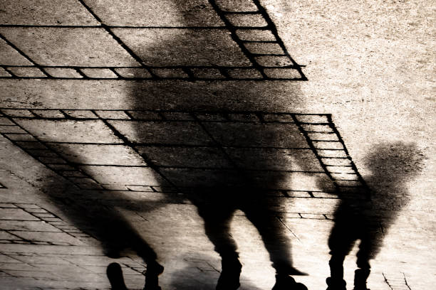 Silhouette shadow of a father holding hands with two small boys stock photo