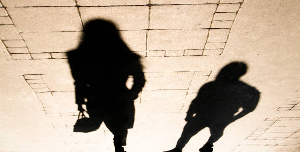 Silhouette shadow of a woman and a man on city sidewalk