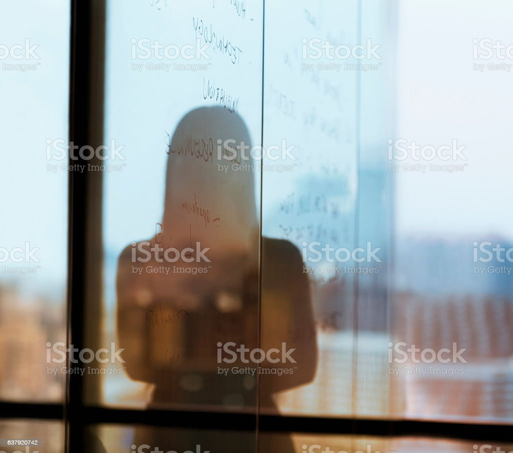 Silhouette shadow of woman looking at city from office stock photo