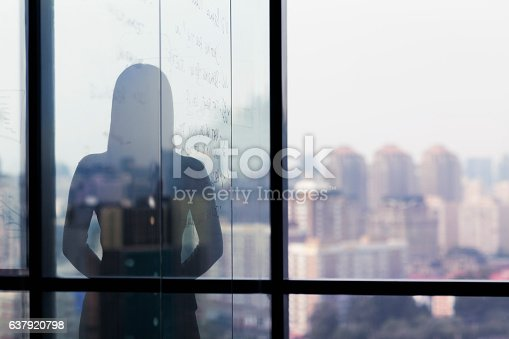 1068588904 istock photo Silhouette shadow of woman looking at city from office 637920798