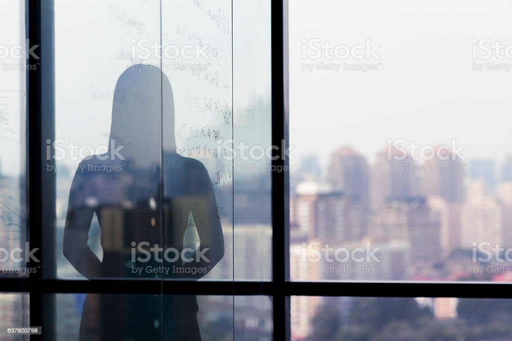 Silhouette shadow of woman looking at city from office – Foto