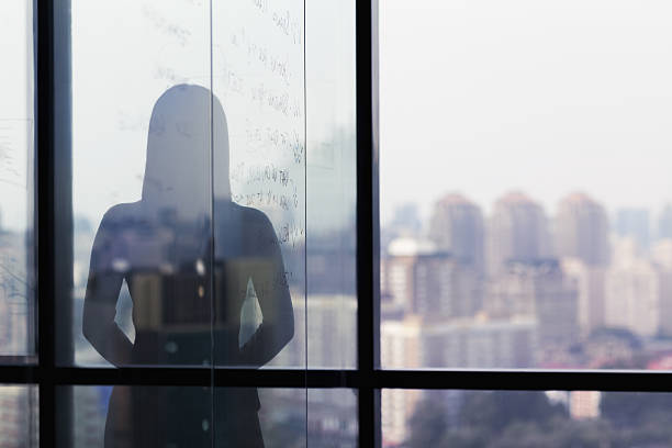 Silhouette shadow of woman looking at city from office - Photo