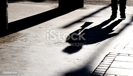 Silhouette shadows of a person walking in city street passage  in black and white