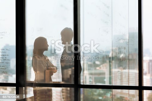 istock Silhouette shadows of business people looking at city in office 637920508