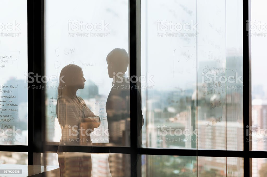 Silhouette shadows of business people looking at city in office stock photo