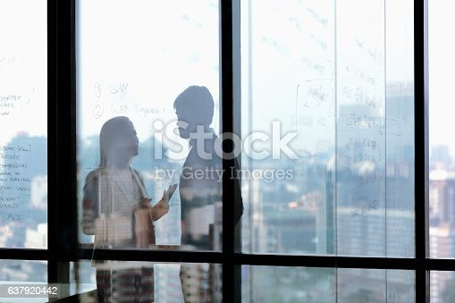 istock Silhouette shadows of business people talking in office 637920442