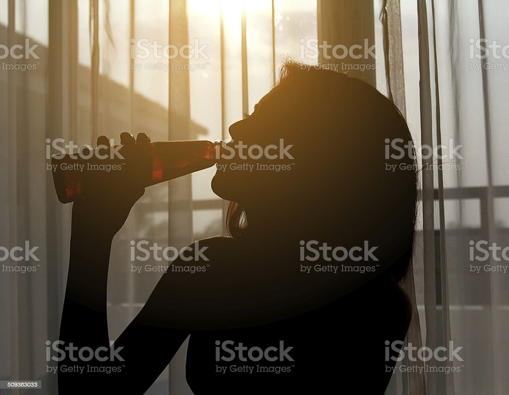 Silhouette shot of a female drinking red wine in a  room stock photo