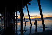 Silhouette shot of Asian man tourist looking at beautiful sunset under bridge structure of Pismo pier at Pismo beach, California, USA. Summer vacation travel concept