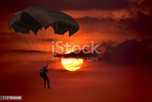 Silhouette skydiver control with  parachute in sunset  sky background with dark cloudy