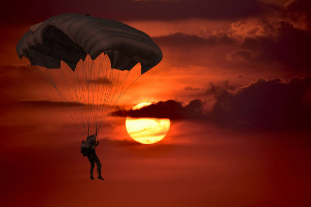 Silhouette skydiver control with  parachute Silhouette skydiver control with  parachute in sunset  sky background with dark cloudy parachuting stock pictures, royalty-free photos & images