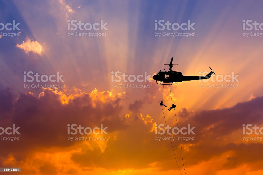 silhouette soldiers in action rappelling from helicopter on sunset stock photo