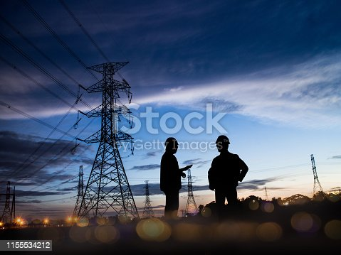 istock Silhouette Successful male engineer standing survey work on construction over blurred high-voltage pylons and construction. examination, inspection, survey 1155534212