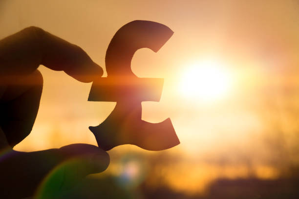 silhouette symbol of the British pound sterling in hand against stock photo