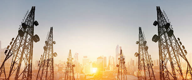Silhouette, telecommunication towers with TV antennas and cityscape in sunrise - foto de stock