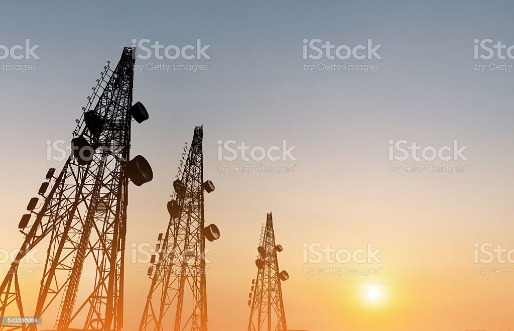 Silhouette, telecommunication towers with TV antennas, satellite dish in sunset - foto de acervo
