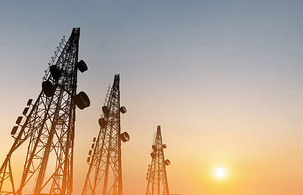 Silhouette, telecommunication towers with TV antennas, satellite dish in sunset - foto de stock
