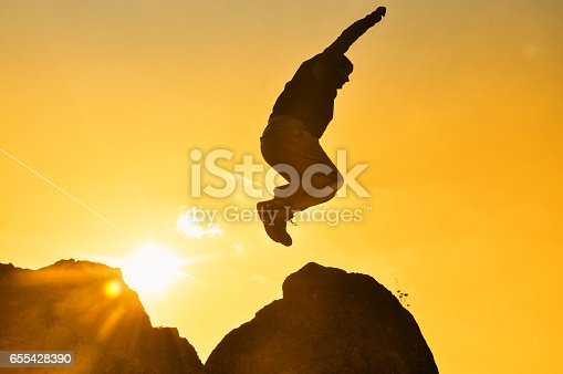 Concept of successful man on top of the hill into the sun