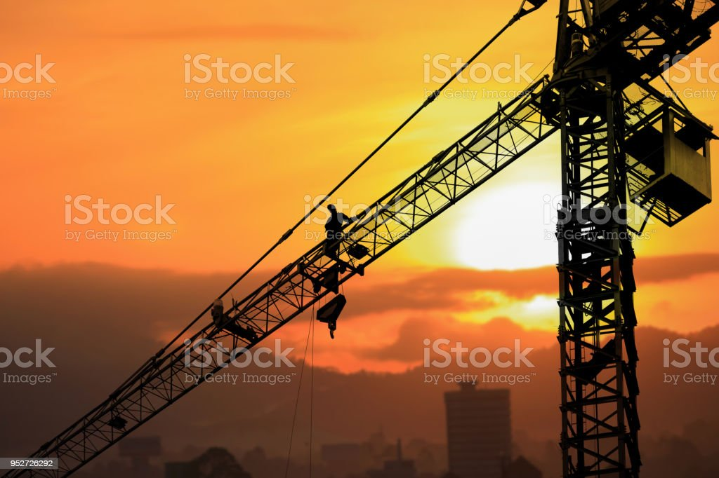 Silhouette Tower crane construction with worker in sunset and copy space add text Silhouette Tower crane construction with worker in sunset and copy space add text Architect Stock Photo
